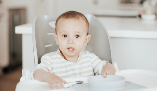Six month old baby sitting in high chair ready to eat iron-rich foods