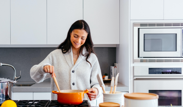 woman cooking on the stove trying to improve egg health for pregnancy