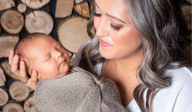 Smiling postpartum mom holding new baby wrapped in swaddle