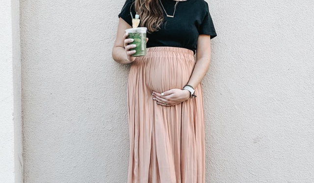 Pregnant woman standing against wall with high vitamin A smoothie in her hand
