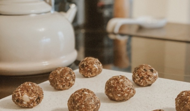 Homemade cookies and cream energy balls for pregnancy and postpartum sitting on the counter beside a white kettle