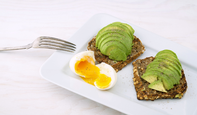 Whole grain toast topped with avocado and soft boiled egg on the side for nutrition for postpartum healing