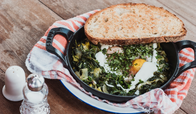 eggs and spinach in cast iron pan with slice of bread on the side