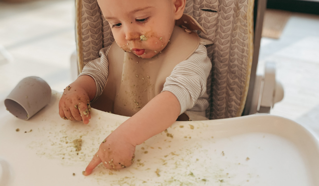 Infant sitting in highchair playing with food on tray